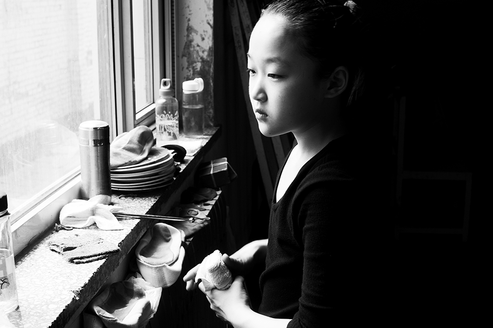 A young apprentee looks out of a window after the daily training in an acrobats school in Wuqiao.