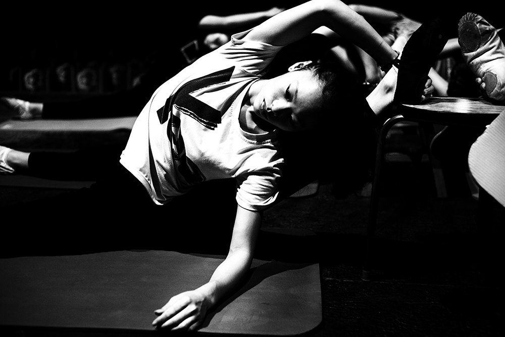 A young performer stretches during rehearsals for a show in Beijing.
