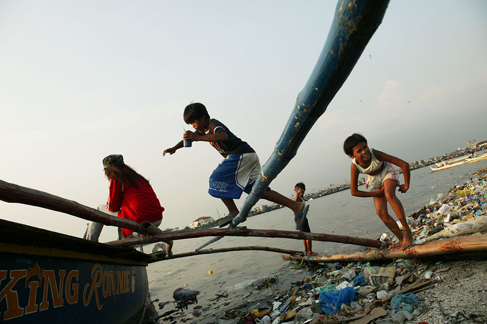 Children living in the Baseco slum play among waste, Metro Manila, Philippines.In Metro Manila an estimated 37 % of the population or over 4.0 million Filippinos lived in slums in 2010 and slum population growth rate is at 8 % annually according to a report by the Philippine Institute for Development Studies.Urban environmental problems such as air pollution, water pollution, flooding and congestion are more pronounced in city slums. Slum dwellers' living conditions depict poverty in terms of both inadequate incomes and environmental deprivation. The Baseco slum, for example has been built directly on reclaimed swampland behind and on top of the sea wall which protects the Baseco Bay. This settlement is particularly vulnerable to hurricanes and tsunamis due to its location. The Philippines are considered one of the most disaster prone regions worldwide. The country ranks 12th among the 200 countries most at risk for tropical cyclones, floods, earthquakes and landslides according to the 2009 Mortality Risk Index of the UN International Strategy for Disaster Reduction. The impact of climate change is likely to increase the occurence of extreme weather conditions. The urban environmentally poor would be suffering more from the changes than other groups of urban dwellers since they are most exposed to natural disasters. (Archival photo)Photo by @hessekatharina #climatechange#climatechangeisreal#slums#baseco#philippines#povertyandclimatechange#katharinahesse