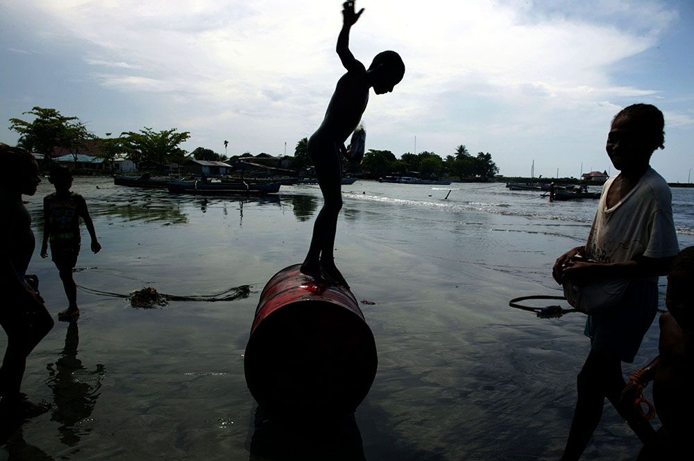 A child plays with an empty fuel barrel at the beach in Sarmi, West Papua. In the Sarmi region of Papua , attempts from national and foreign companies to buy the rainforest have been turned down by Sarmi's govenor. (Logging is one of the major causes of destruction in West Papua). He thinks it's not a solution to destroy Papua's rainforest and replace it with oil palm plantations as those take about eight years to grow until the first harvest. He rather encourages Indonesians from other islands like Java and Sumatra to move to Papua and find jobs in the fishing industry or settle in the rainforest. Should the government ever try to allow companies to explore the rainforest in Sarmi , there'd {quote}be trouble{quote} with the locals. Sarmi is seen as a positive alternative to the destruction of the rainforest in other parts of Papua . Photo by @hessekatharina #newguinea #papua #climatechange #climatechangeisreal #logging
