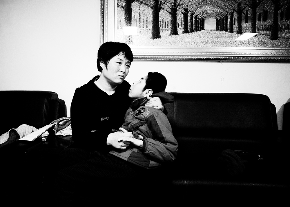 Beijing, March 11, 2015 : Tian Peng, 15, is taken care of by his mother Cui Xinying while his little brother Tian Ye, 3, plays in the apartment.As a baby Tian Peng fell ill with brain   hemorrhage supposedly due to a lack of vitamin K. When Tian Peng was a kid, friends advised the parents to simply abandon him as there\'s neither enough help nor support in China apart from a small NGO. Tian is unable to speak, think, walk and needs help for everything.Chinese attitudes towards people with disabilities have improved in recent years, but the support of society and opportunities in education and employment are scarce.