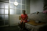 August 2007 : a woman sits in her tiny one bedroom before it is demolished....