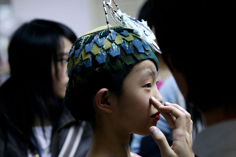 A Chinese ballet student has her make-up adjusted in the dressing room before final rehearsals with the renowned Teatro alla Scala Ballet in Beijing, November 8, 2006, China