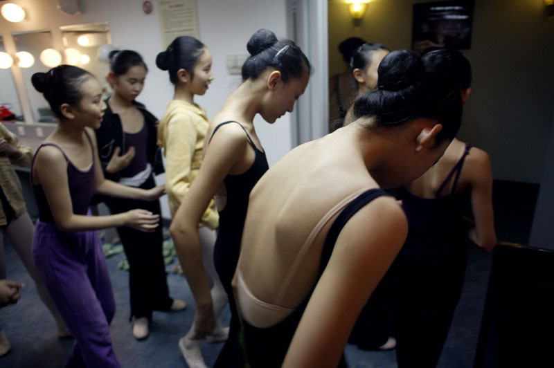 Chinese ballet students change clothes in the dressing room before final rehearsals with the renowned Teatro alla Scala Ballet in Beijing, November 8, 2006, China. The Teatro alla Scala tours China for the first time and performs a Midsummer Night's dream