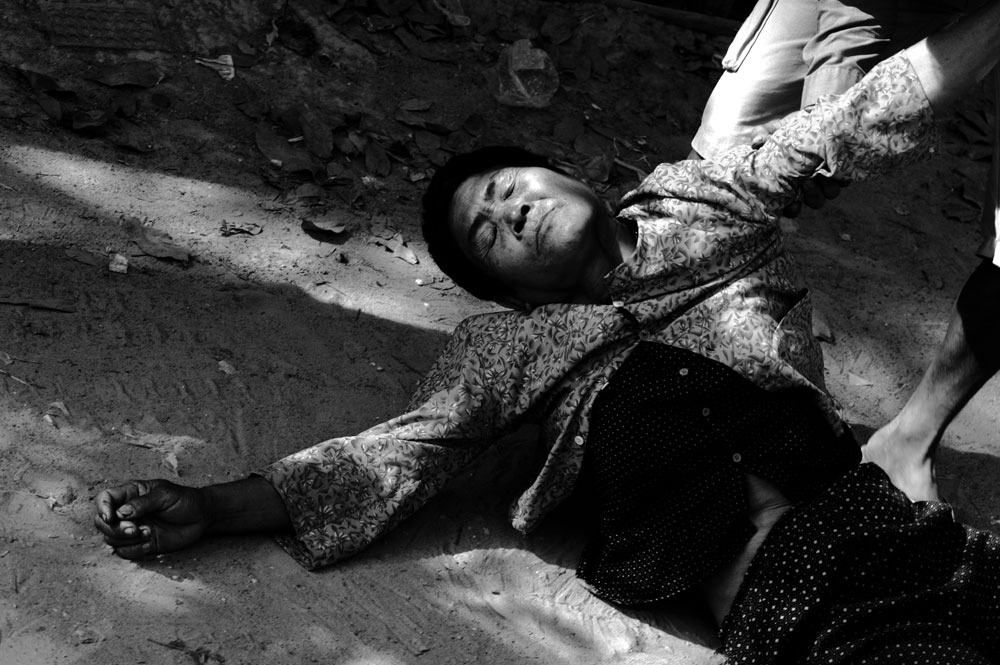 Siem Reap, February - 2008: a  woman who's one of the many refugee returnees, collapses in a street .