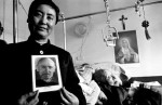 Sister Francis shows a picture of foreign missionary Vincent Lebbe.  Father Lebbe trained the 98-year-old priest in the backgroundHebei province