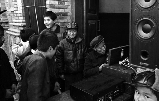 church layman installs loudspeakers outside the church while children look on. Shaanxi province