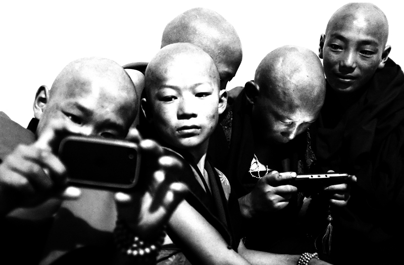 Gansu province, April 2012 : novices play with electronic devices in a hotel dorm.