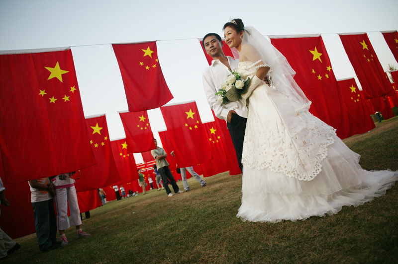 A newly wed couple poses for a souvenir picture in a park on October 1, 2006, Beijing.