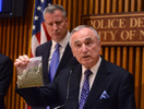 NYC Police Commissioner William Bratten, right holds a bag of oregano simulating 25 grams of marijuana during a press conference announcing news guidelines regarding small amounts of marijuana possesion. Mayor Bill deBlasio is at left One Police Plaza  Monday November 10, 2014