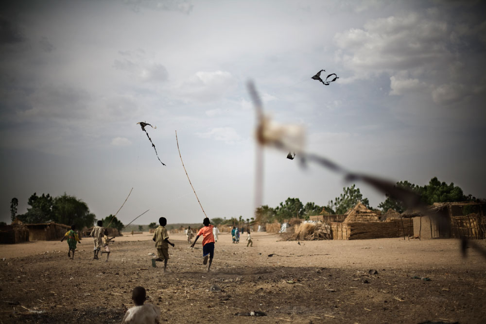Children flying kites made from plastic bags, Goz Amer Refugee Camp, Eastern Chad.