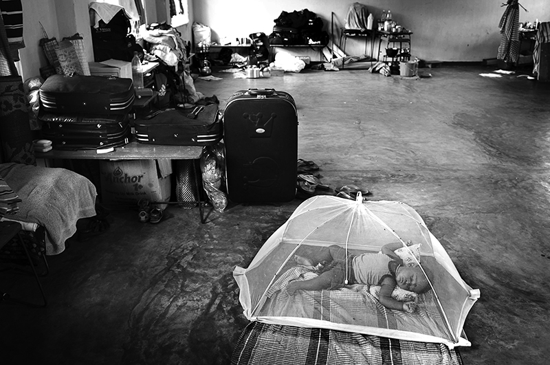 child sleeps under the mosquito net in the classroom turned into a camp for the displaced people in Trincomalee, Sri Lanka