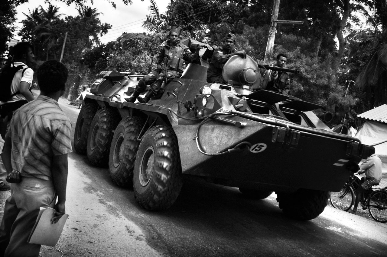 An IDP looks on as the Sri Lankan Army personel carrier heads towards Muttur where fierce fighting escalated between Tamil Tiger rebels and the Sri Lankan Army. Some 45,000 people left Muttur town in seek of safer area in Kanthale, Trincomalee in August 2006.
