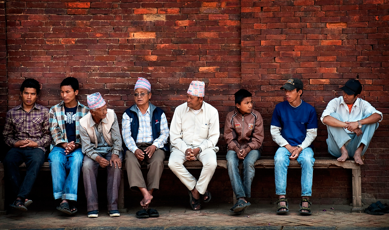Men and boys sit on the bench at the Patan Durbar square.Patan Durbar square is situated in the heart of the city. The square is full of ancient monumenets, temples and shrines, noted for their exquisite craftsmanship and architectural beauty.