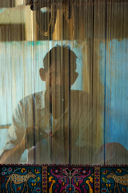 A man working on the  weaving loom.