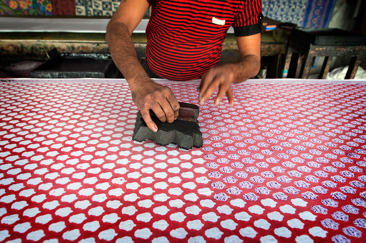 A worker  uses the wooden handle to make color patterns on cotton cloth in the Jaipur cooperative for cotton and carpet production. The colors used are natural and paintings of fabrics are done manually.