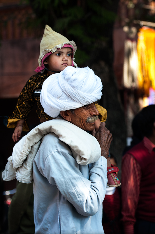 An elderly man holds a child on his shoulder in Jaipur, Rajastan.
