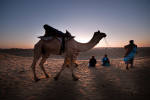 Jaisalmer desert.Doud Khan, a camel handler talks to a tourist while waiting the sunset over the sand dunes in Jaisalmer desert which is the main attraction.