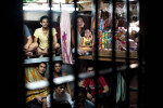 A child sits on her father's lap while in the overcrowded cell of male inmates.