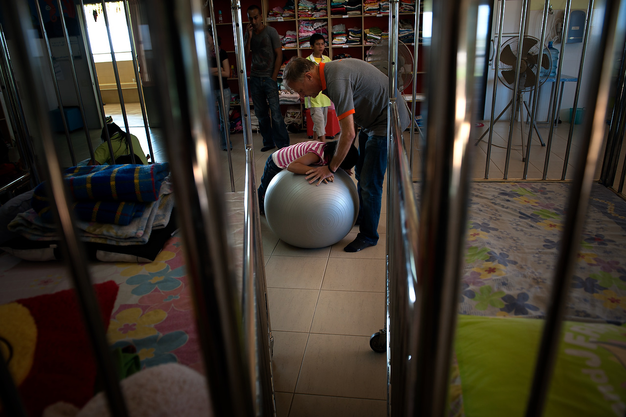 "Alan, a full-time volunteer of 6 months with a background in nursing and orthopedics, plays with a visually-impaired child using a medical ball. ""The most important thing is to show them love,"" he explains on the topic of physical rehabilitation. Specialists are very difficult to find in Thailand due to social stigmas; working with disabilities is not a popular subject at medicine schools."