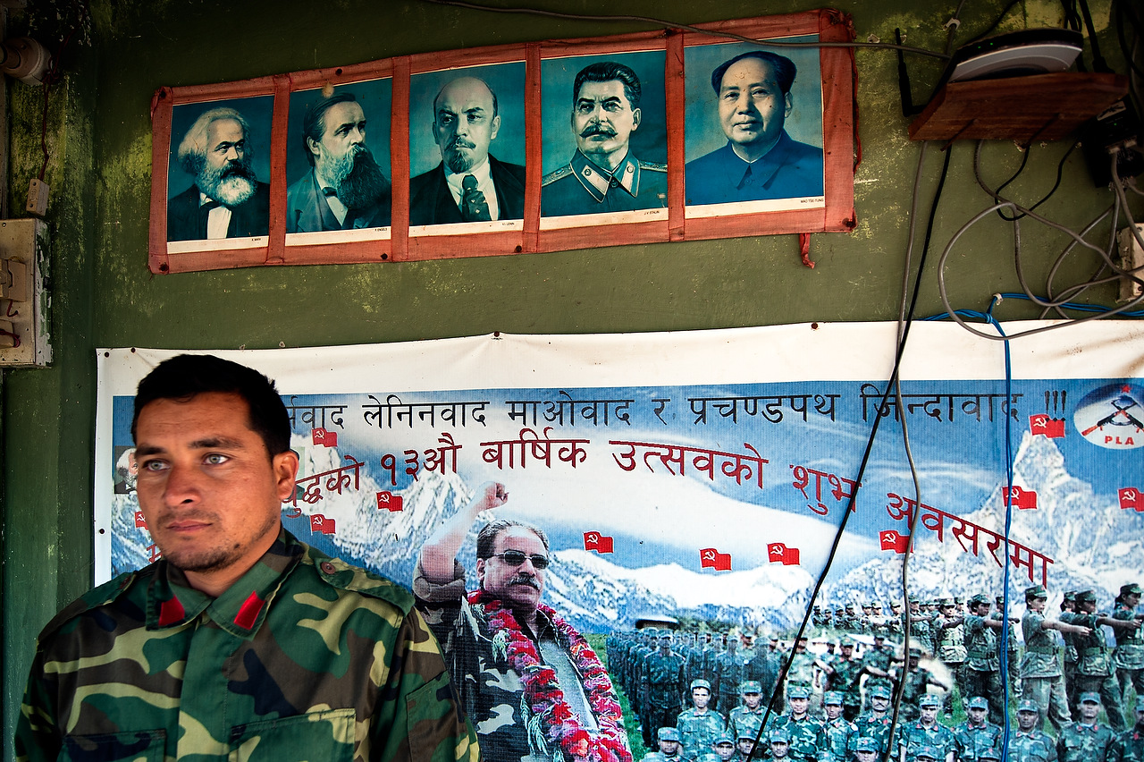 Deputy brigade commander of the Lishengam memorial brigade of People's Liberation Army, Major Aasha Chaudasi in front of a dormitory wall decorated with photos of Marx, Engels, Lenin, Stalin, chairman Mao and Nepal Maoist chairman Prachanda in Kilali PLA cantonment in far western region of Nepal.
