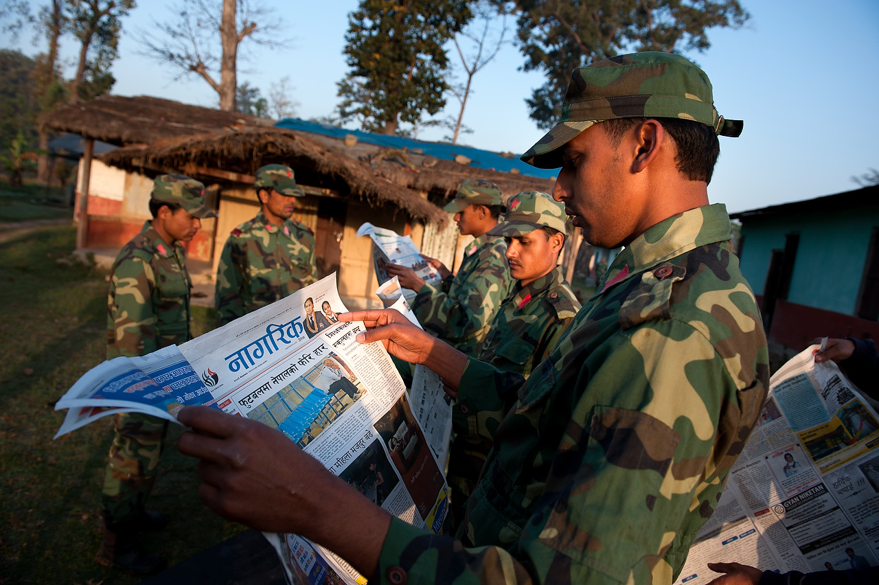 A PLA fighter reads at loud for its comrades news paper articles during the break between training activities in Lishengam memorial brigade cantonment in Kilali far western region of Nepal.