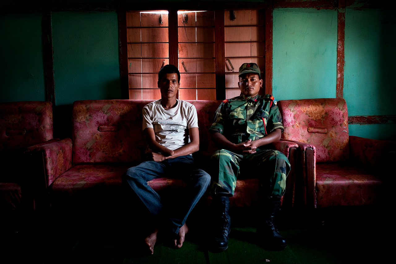 PLA fighter Shangharsha Deuwa (Left) sits beside its comrade medical doctor Manraj Shahi who amputated his right hand in 2005. Shanharsha joined Maoists guerrillas when he was 17 years of age since then he got involved in making improvised explosive devices. He lost his right hand while making a land mine.
