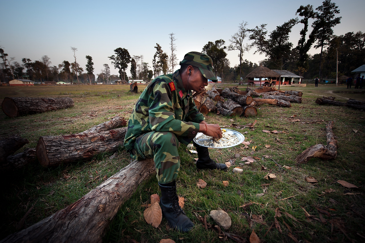 A PLA fighter eats dinner while sits on the log in PLA cantonment in Kilali, far western region of Nepal.