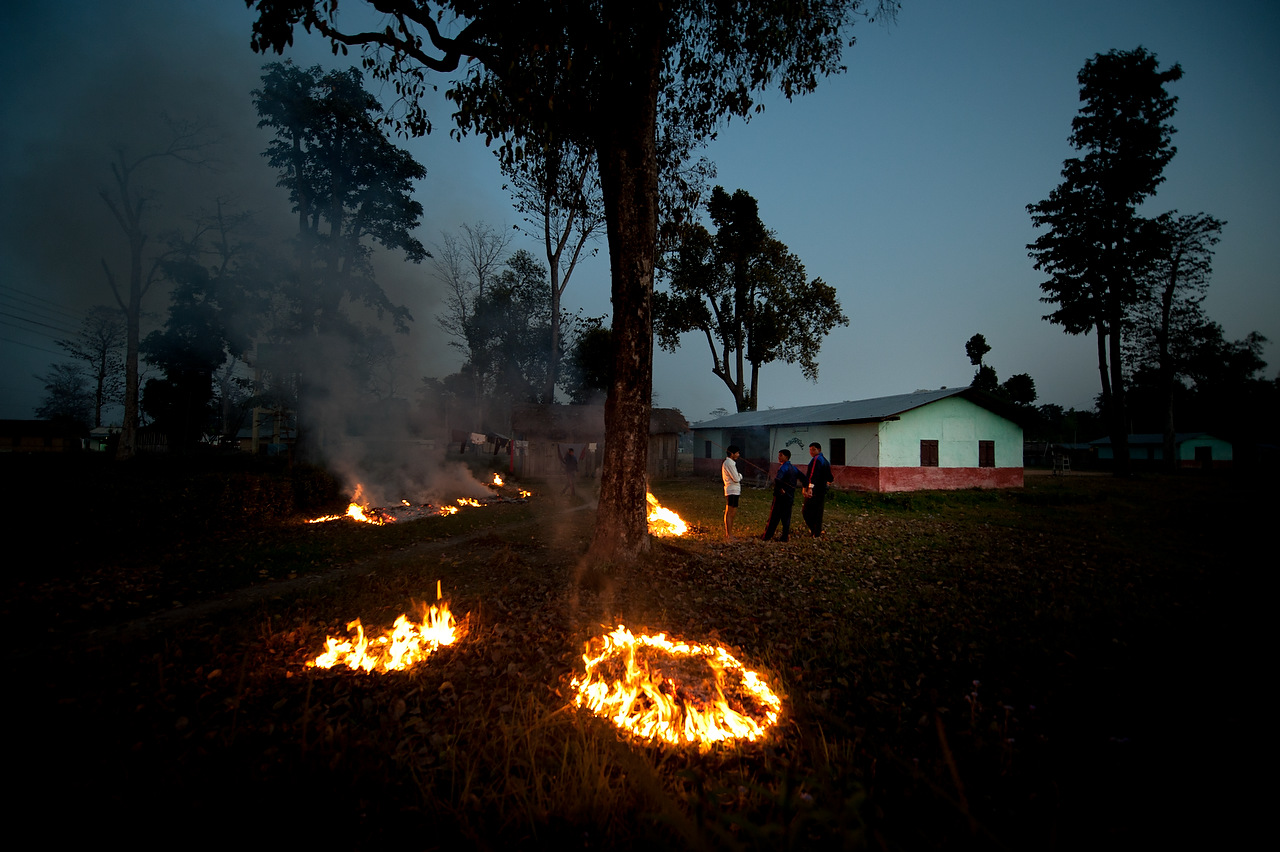 As the night falls, PLA fighters chatt while burning trash in the Lishengam memorial brigade PLA cantonment compound in Kilali, far western region, NEpal.