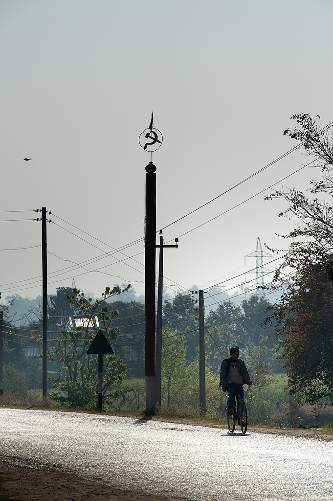 A man rides a bike while sickle and hammer, symbol of Communists is placed on the pole on the entrance into a village of Gorange, far wester region of Nepal.Maoist guerrilla gained popularity mainly in rural and remote areas of Nepal.