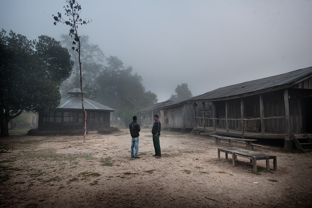 Two elephant handlers talk in front of their accommodation barracks in the compound of the Hattisar Soura elephant stable in Chitwan, Nepal.