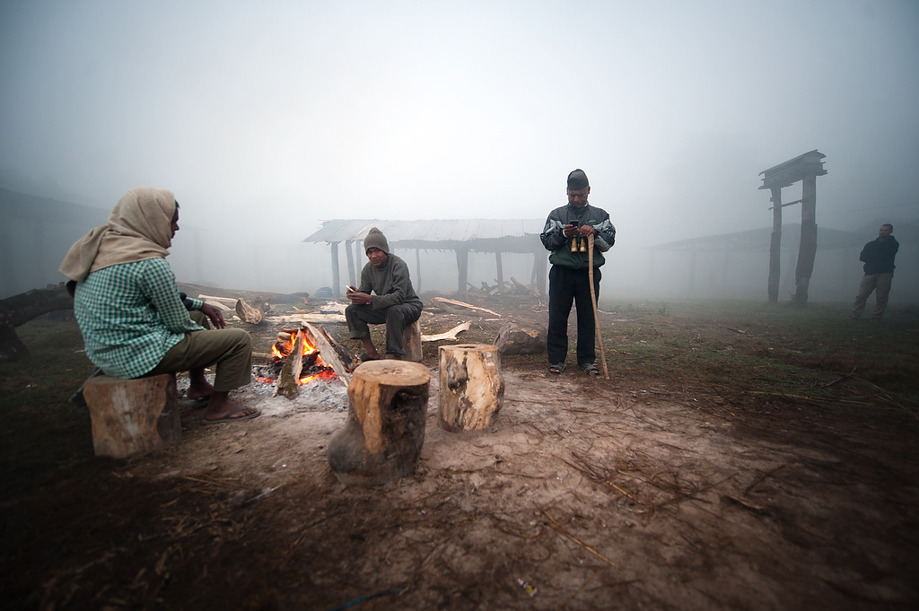 Mahouts sit by the camp fire while a tourist guite checks his mobile phone.
