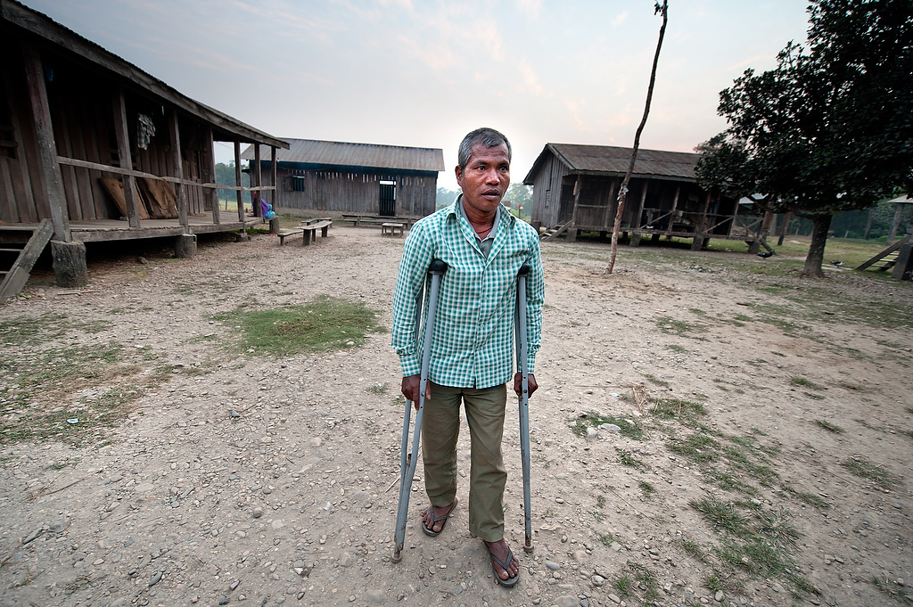 Shankar Chowdhary helps himself to walk with cane inside the mahouts compound. Shankar has been elephant handler for 19 years. A year and half ago he was injured by the elephant of his colleague while attending his own elephant. The other elephant hit him with his tusks before stepping on his leg. Injuries caused by the elephant rendered him incapacitated up to today and can't ride an elephant.Elephant stable, Hattisar Soura, has 16 elephants and 30 handlers. Among elephant handlers there are also two female handlers. It is the state run stable and the government appoints all employees.  The stable caters mainly tourists for safari in Chitwan national park. Elephant handlers live in compound with very basic facilities. None of the mahouts has families living with them in a stable except one whose children live with him in order to attend the school in the village. With the wages not exceeding USD 15 per month, mahouts and their families live on the brink of existence.