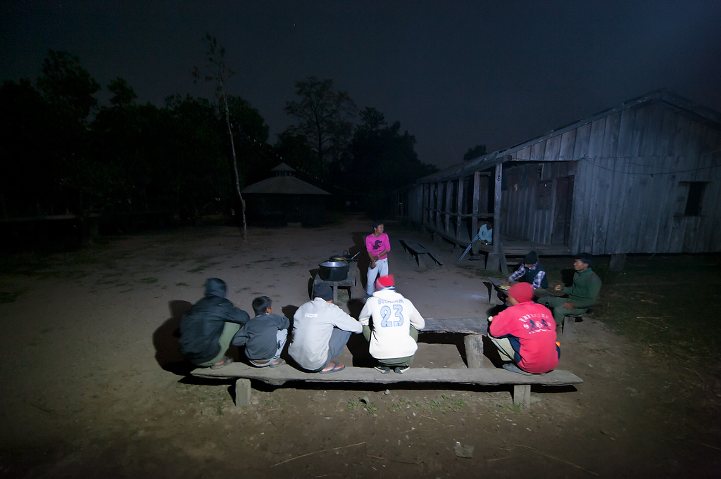 Mahouts gather around the makeshift table to eat dinner at Hattisar Soura elephant stable