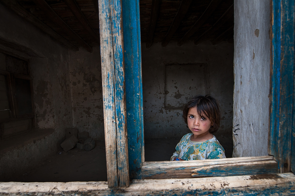 "A little girl looks through the window of the CMAM clinic run by Unicef Partner ACF in Kabul, Afghanistan.In Afghanistan 2.7 million children are stunted. For more than two decades interaction of conflict, destructive political processes and natural disasters have caused destruction and breakdown of basic infrastructure,such as, health and education facilities.UNICEF with the support of partners is working in 22 provinces of Afghanistan on treatment of severe acute malnutrition through community-based management of acute malnutrition program, also known as CMAM. In this program the children come to clinic once a week, are monitored on their progress and given enough ""special therapeutic food"" to eat at home until their next visit."