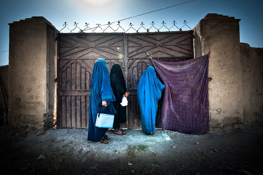 Female team of vaccinators in front of the gate of the house where children are to be vaccinated. Female polio front-line workers hold the key to eradicating polio from   Afghanistan. Able to speak woman to woman; they convince mothers to vaccinate their children. They are 12% of Afghanistan's campaign workers.In socially conservative communities where polio still persists today, cultural norms often do not allow male vaccinators to enter a home, or even communicate with women on the doorstep.Newborns, children who are sick or sleeping are often missed.The Global Polio Eradication Initiative (PEI) that aims to Eradicate Poliomyelitis, a crippling disease effecting children has now entered its most critical and hopefully the final phase. The impressive success of the initiative including reduction in the number of cases from 350,000 in 1988 to less than 223 in 2012 and in number of endemic countries from over 125 in 1988 to just three by end 2012 is commendable. The success of the Global PEI, which was launched in 1988, depends now on interruption of Wild Polio Virus (WPV) circulation in the last three endemic countries – Afghanistan, Nigeria and Pakistan. Following years of decline and stagnation in the number of cases with just 25 case reported in 2010, Afghanistan had a major outbreak in 2011 which brought home the need to scale up steps to improve campaign quality and to get Afghans from all walks of life involved in contributing to this national cause.The 2011 out break resulted in 80 cases from all regions of the country and over 30 districts. In 2012, 30 cases were reported and in 2013 to date only 3 cases have been reported so far.??Historically, South region is the only region of the country to have never succeeded in interrupting virus circulation and has always had the highest burden of cases with between 70 to 85 percent of all cases reported in the last decade reported from this region. Although the region has not reported any case since November 2012 it is too soon to start celebrating.?All 3 cases reported in Afghanistan in 2013 have been reported from the East region - 2 from Nangarhar province and 1 from Kunar.