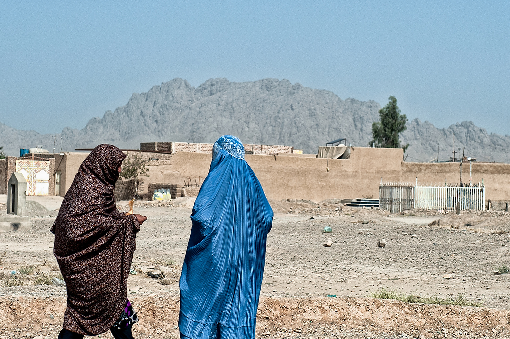 Two female social mobilizers walk past the cemetery  on their way to start their polio mobilising work in the suburbs of Kandahar.Female polio front-line workers hold the key to eradicating polio from   Afghanistan. Able to speak woman to woman; they convince mothers to vaccinate their children. They are 12% of Afghanistan's campaign workers.In socially conservative communities where polio still persists today, cultural norms often do not allow male vaccinators to enter a home, or even communicate with women on the doorstep.Newborns, children who are sick or sleeping are often missed.The Global Polio Eradication Initiative (PEI) that aims to Eradicate Poliomyelitis, a crippling disease effecting children has now entered its most critical and hopefully the final phase. The impressive success of the initiative including reduction in the number of cases from 350,000 in 1988 to less than 223 in 2012 and in number of endemic countries from over 125 in 1988 to just three by end 2012 is commendable. The success of the Global PEI, which was launched in 1988, depends now on interruption of Wild Polio Virus (WPV) circulation in the last three endemic countries – Afghanistan, Nigeria and Pakistan. Following years of decline and stagnation in the number of cases with just 25 case reported in 2010, Afghanistan had a major outbreak in 2011 which brought home the need to scale up steps to improve campaign quality and to get Afghans from all walks of life involved in contributing to this national cause.The 2011 out break resulted in 80 cases from all regions of the country and over 30 districts. In 2012, 30 cases were reported and in 2013 to date only 3 cases have been reported so far.??Historically, South region is the only region of the country to have never succeeded in interrupting virus circulation and has always had the highest burden of cases with between 70 to 85 percent of all cases reported in the last decade reported from this region. Although the region has not reported