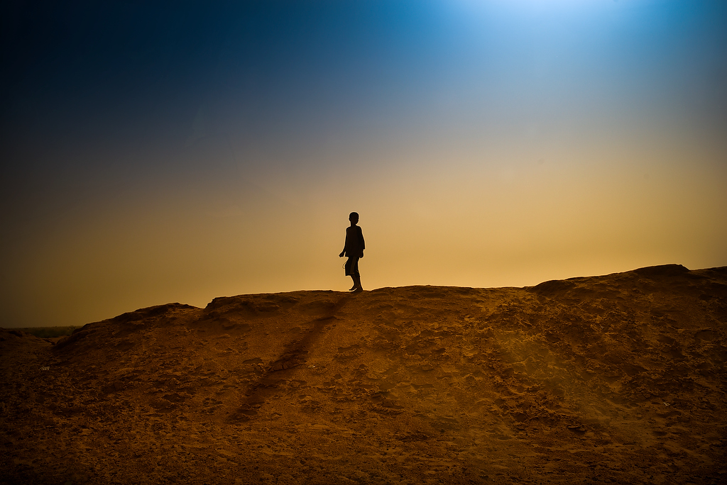 A boy walks on the sand bank surrounding M\'Bera refugee camp. M'bera, Mauritania.Mauritania is the largest recipient of refugees fleeing the crisis in Mali. There are around 53,474 Malian refugees in M{quote}bera camp, 58 per cent of them children under 18.