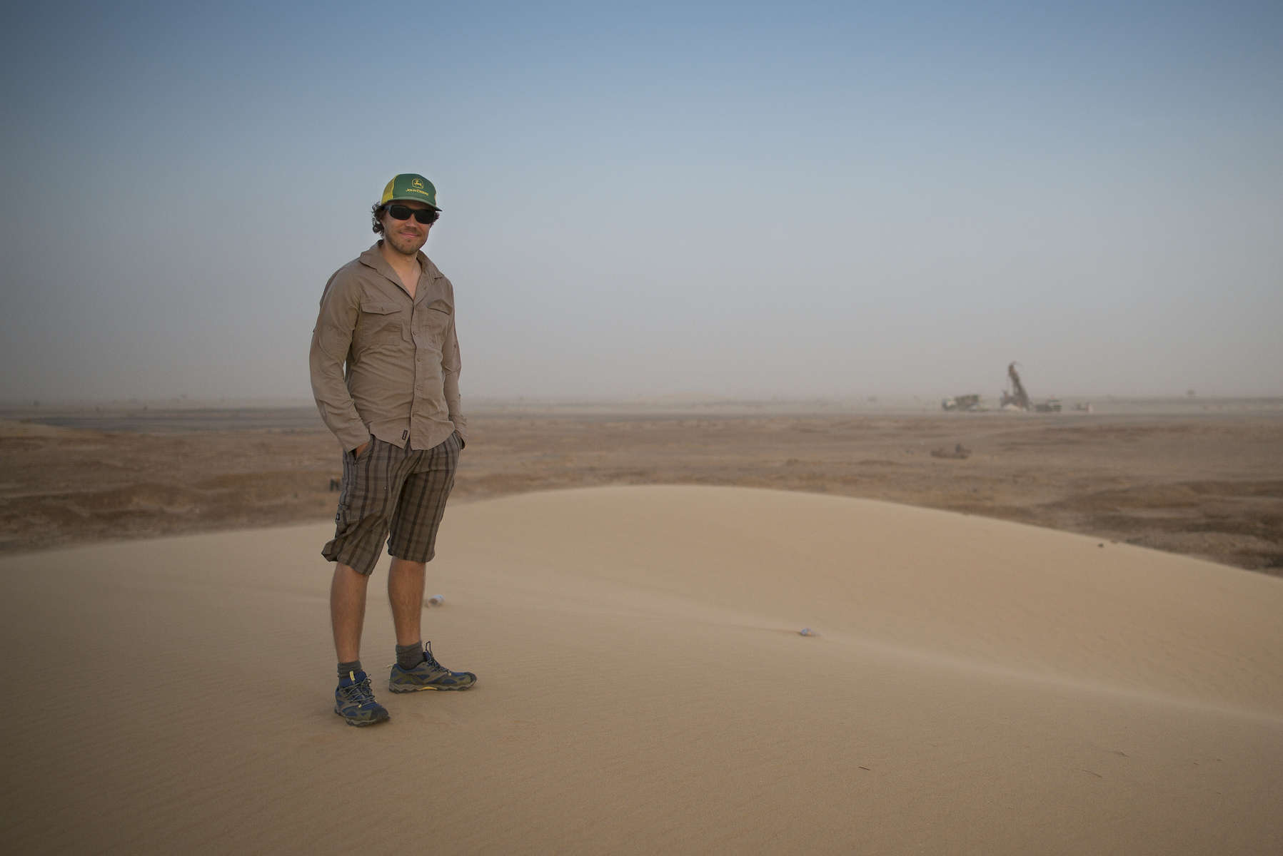 AlGold Resources LTD Geologist Alastair Gallaugher stands on the sand dune while in a distance the reverse circulation drilling rig can be seen. Tijirit, Mauritania.The Tijirit Project is Algold Resource's Flagship property in Mauritania located within the Inchiri Region, 4 hours drive north of the Capital Nouakchott.  Exploration is currently underway throughout the property with the aim to increase mineral resources from the current Ni 43-101 compliant mineral resource of 28,930 ounces at a grade of 1.75 g/t Au (M&I) and inferred resources of 241,560 ounces at a grade of 1.71 g/t Au at a cut-off grade of 1.0 g/t Au