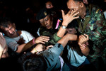 Thai soldiers protect a man allegedly suspected to be involved in explosions from angry crowd of pro-government group on April 22, 2010 in Bangkok, Thailand.