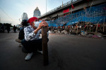 An anti government protester holds a piece of wood  inside fortified red shirt area in Silom, Bangkok's financial district as the anti government protesters are seen gearing up to brace for possible army crack down on 26 April 2010 Bangkok ThailandThai political crisis have been plunged into further uncertainty as the Prime Minister Vejjajiva rejected UDD's proposal to disolve the parliament and call for the ballot elections within 90 days. Prime ministers statement left red shirts to brace for the imminent crack down by the Army and the police.