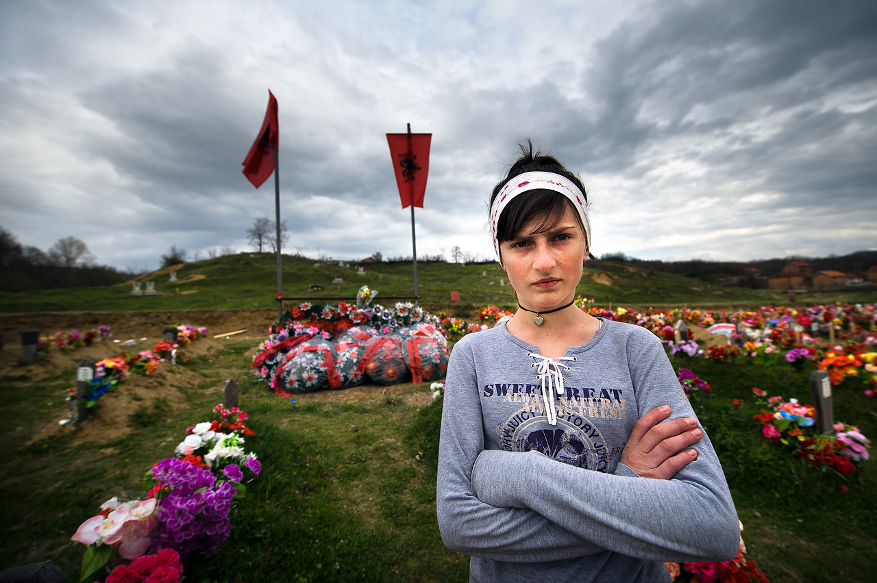 Luljeta Duraku in front of graves of 241 Kosovar Albanians who were massacred by Serbian forces between 25 and 27 March 1999.