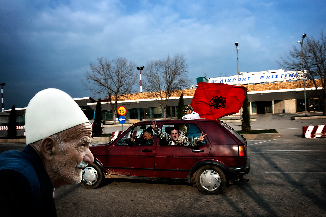 An old man passes by while jubilant crowd gathered to greet former prime minister of Kosova, Ramush Haradinaj who has been released from UN Tribunal for war crimes on 03 April 2008, Prishtina airport Prishtina, Kosova.