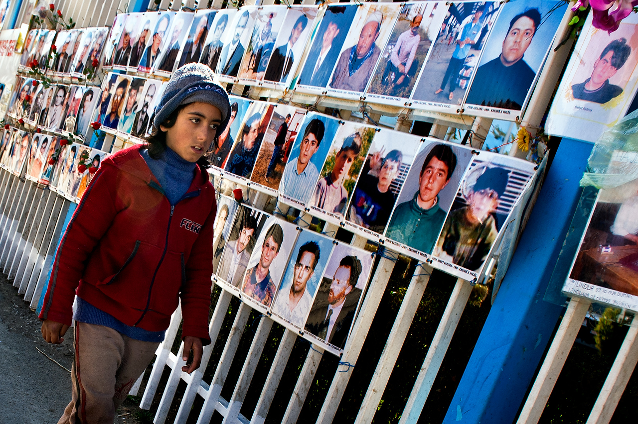 Prishtina, Kosova.A young boy walks by photographs of the missing persons who were never found since the 1999 war. Photographs are displayed by the families of the missing persons and and every year members of the family place flowers nearby. Photographs are displayed since 1999 on the fences of the Government building in Prishtina Kosova