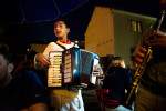Young boy plays accordian entertaining guests in the local caffe.