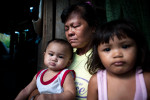 Labangan, Zamboanga del Sur, Mindanao Philippines.Noria Gonzagon Samal (46) wife of the killed driver  cries while holds two minor children.Dozen of supporters of the Liberal party candidate for mayor Willson Nandang where heading to campaign rally when group of armed men in bonnets ordered supporters to leave the scene while they killed a driver, Abubakar Padino Somal (47) was killed in Nuburan village, Langapod municipality.Intimidation, harassment and killing of the supporters of the political rivals in Mindanao are increasing amid impending presidential and general elections in Philippines. Political dynasties of powerful clans in Mindanao, southern restive province of Philippines, continue to use private armies to intimidate supporters of the rival candidates.