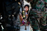 A child watches members of the special police force during the raid which was allegedly orchestrated by the opponent political candidate during the election campaign in Maguindanao.