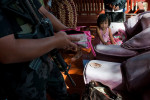 A child watches member of the special police force as he checks her mothers belongings during the raid which was allegedly orchestrated by the opponnent political candidate during the election campaign in Maguindanao.