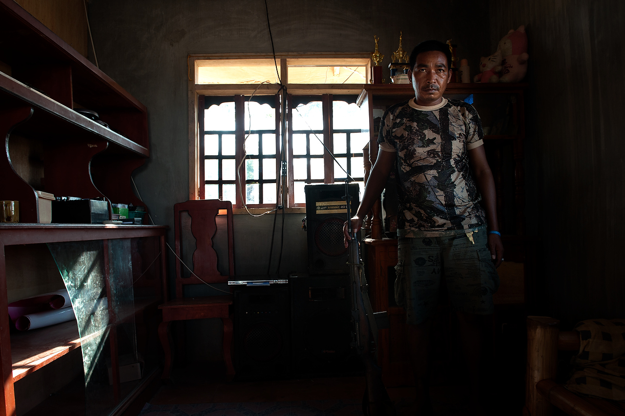 Juditho Unao (37) member of the Civilian Armed Forces Geographical Unit (CAFGU) holds his rifle in a house where was attacked alledgedly by MILF rebels in Datu Hoffer, Maguindanao Philippines.CAFGU is irregular auxilary force of the Armed Forces of Philippines (AFP) and the force was created in 1987 when the Filippino government provided them with weapons to prevent the re-infiltration of insurgents into communities that have already been cleared. By 2007 there were estimated to be some 60,000 CAFGU members active. Number still remains high despite allegations of human rights abuses committed by CAFGU.