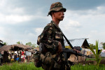 Member of the CAFGU paramilitary unit passes by village of Dattu Hoffer in Maguindanao.CAFGU is irregular auxilary force of the Armed Forces of Philippines (AFP). It was created in 1987 when the Filippino government provided them with weapons to prevent the re-infiltration of insurgents into communities that have already been cleared. By 2007 there were estimated to be some 60,000 CAFGU members active. Number still remains high despite allegations of human rights abuses commited by CAFGU.